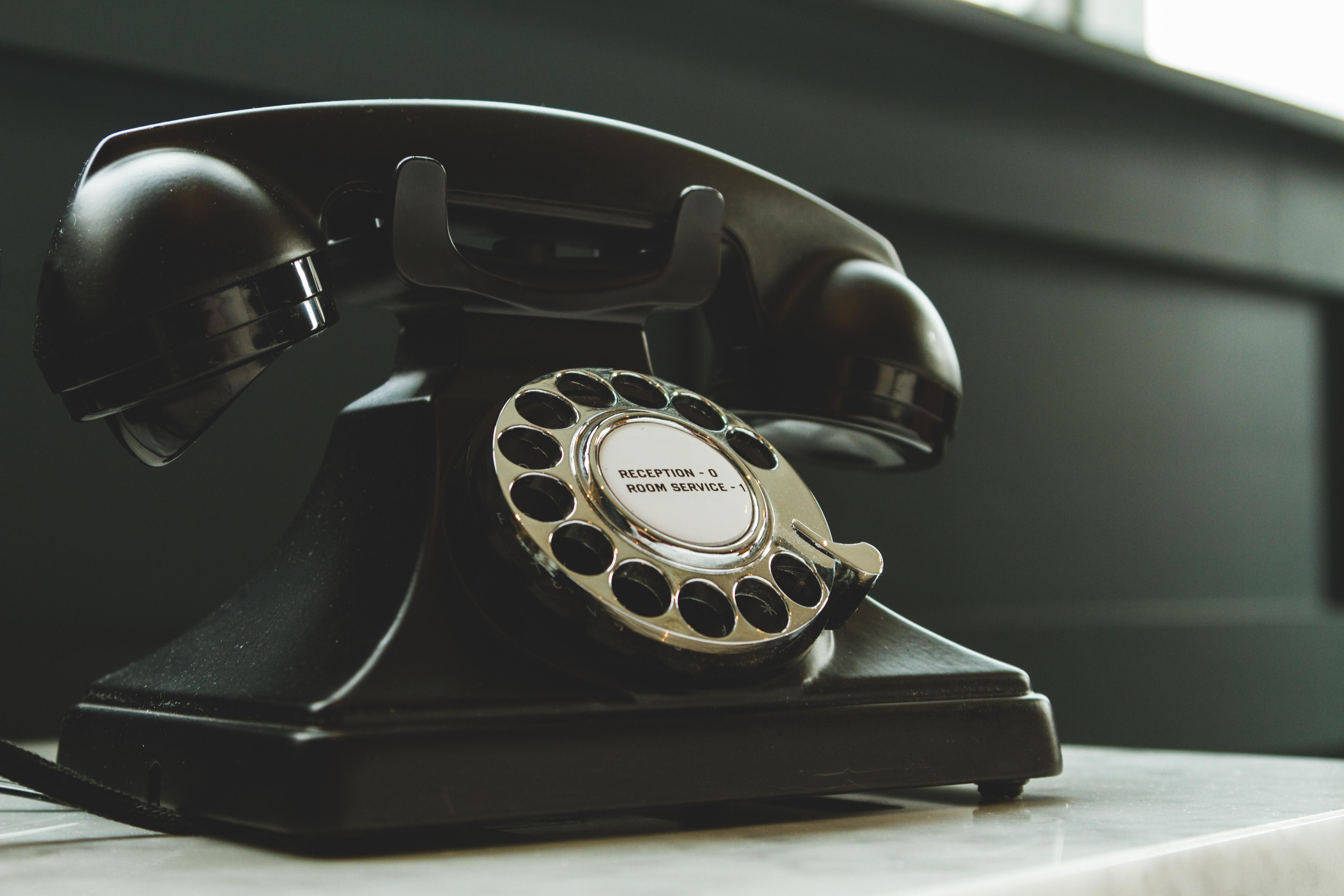 black-rotary-telephone-on-white-surface-1416530