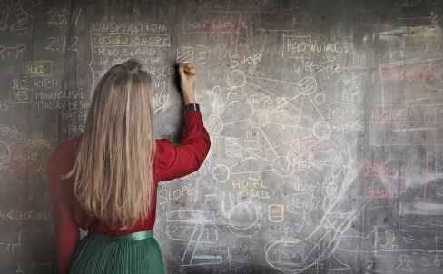 woman in red long sleeve writing on chalk board